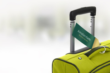 Amsterdam, Netherlands. Green suitcase with label at airport.