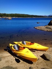 Two yellow kayaks on the shore of a beautiful lake.