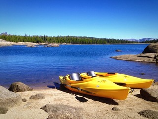 Two yellow kayaks on the shore of a beautiful Mountain Lake.