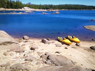 Two kayaks on the shore of a beautiful Mountain Lake.