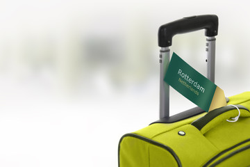 Rotterdam, Netherlands. Green suitcase with label at airport.