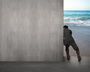 businessman pushing gray concrete wall away