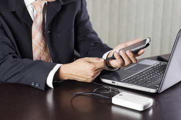 Business man charging his mobile phone