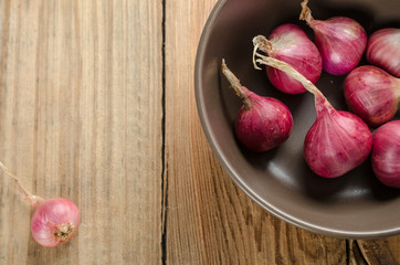 Red onions in brown bowl with empty space for text