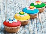 cupcakes covered with mastic on a wooden poster