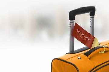 Sacramento, California. Orange suitcase with label at airport.