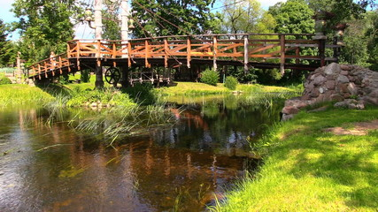 old bridge over fast flowing river and girl in sunny day park