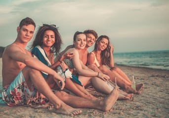 Group of multi ethnic friends with drinks relaxing on a beach