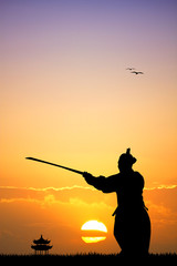Samurai with sword at sunset