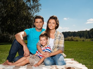 Young family with their child sitting on a blanket outdoors