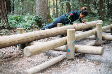 Young woman doing push ups in the woods