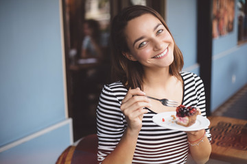 Young woman eating strawberry cheesecake