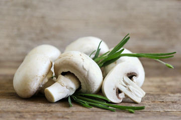 Champignon mushrooms on wooden board with spice branch