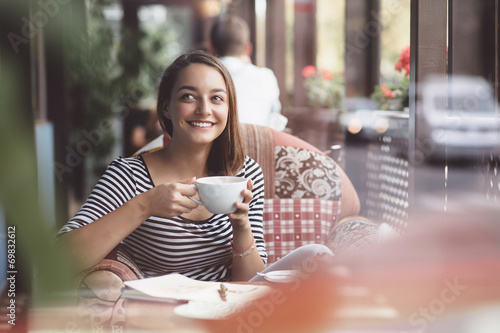 Young woman drinking coffee in urban cafe - 69832612