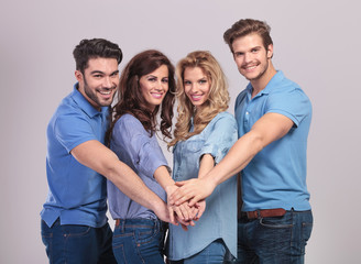 group of people holding hands together as a team