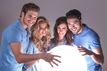 group of people with hands on big ball of light