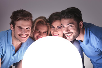 people with faces close to a big ball of light