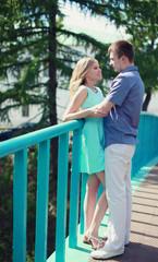 Pretty couple in love on the bridge in the park