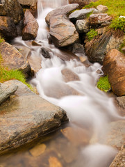 Steep rapid stream of foamy Alpine river. White waves in brook
