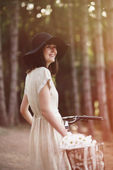 Girl on a bicycle in coniferous forest