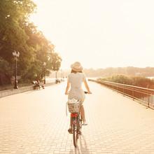Fille à bicyclette dans le parc près du lac. Lightleak effet une