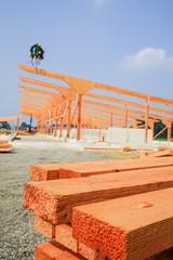 Holzbau, Bauholz mit Binderkonstruktion im Hintergrund