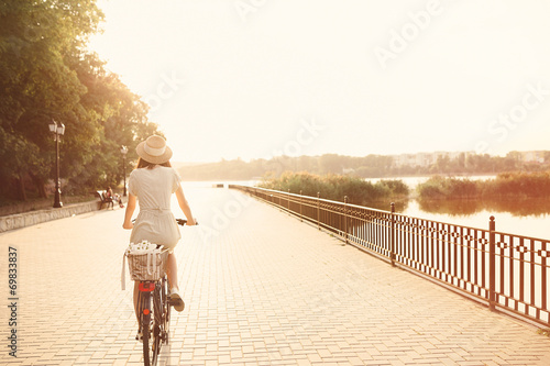 canvas print picture Girl riding a bicycle in park near the lake. Lightleak effect an