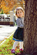 girl hiding behind the tree