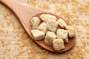 Brown cane sugar cubes in a wooden spoon