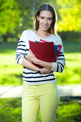 Portrait of smiling business woman with paper folder. Student