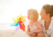 Mother and baby girl playing with colorful windmill toy on the b