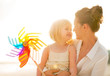 Portrait of mother and baby girl holding colorful windmill toy