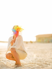 Young woman hiding behind colorful windmill toy on the beach