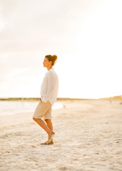 Full length portrait of calm young woman standing on the beach