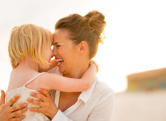 Portrait of smiling mother and baby girl hugging on the beach