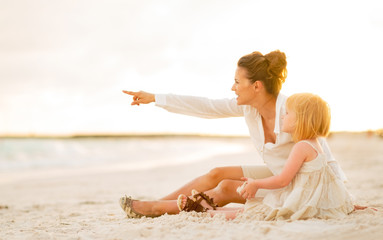 Baby and mother pointing on copy space while sitting on beach