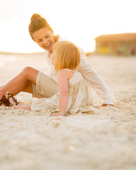 Happy baby girl and mother sitting on the beach in the evening