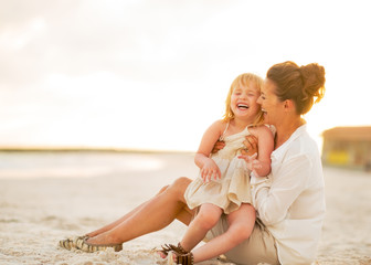 Smiling baby girl and mother sitting on the beach in the evening