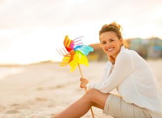 Young woman with colorful windmill toy sitting on the beach
