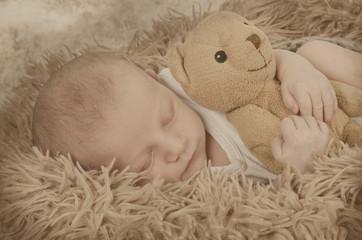 Baby kuschelt mit Teddy