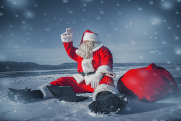 Santa Claus sitting in the snow with a laptop and looking away f