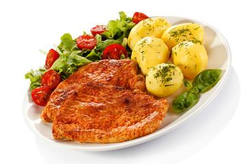 Fried pork chop, boiled potatoes and vegetable salad