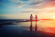 Happy romantic couple walking and holding hands on a beach - 69836428