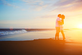 Fototapety Romantic couple kissing on the beach at colorful sunrise