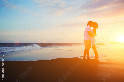 Romantic couple kissing on the beach at colorful sunrise - 69836446