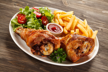 Grilled turkey legs with French fries and vegetables