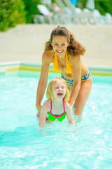 Portrait of happy mother and baby girl playing in swimming pool