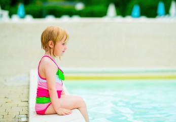 Baby girl sitting near swimming pool