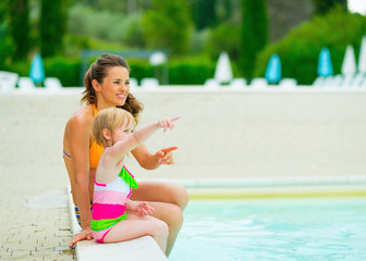 Happy mother and baby girl sitting near swimming pool