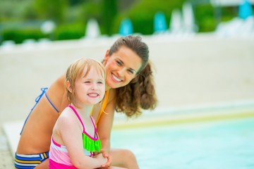 Portrait of mother and baby girl sitting near swimming pool
